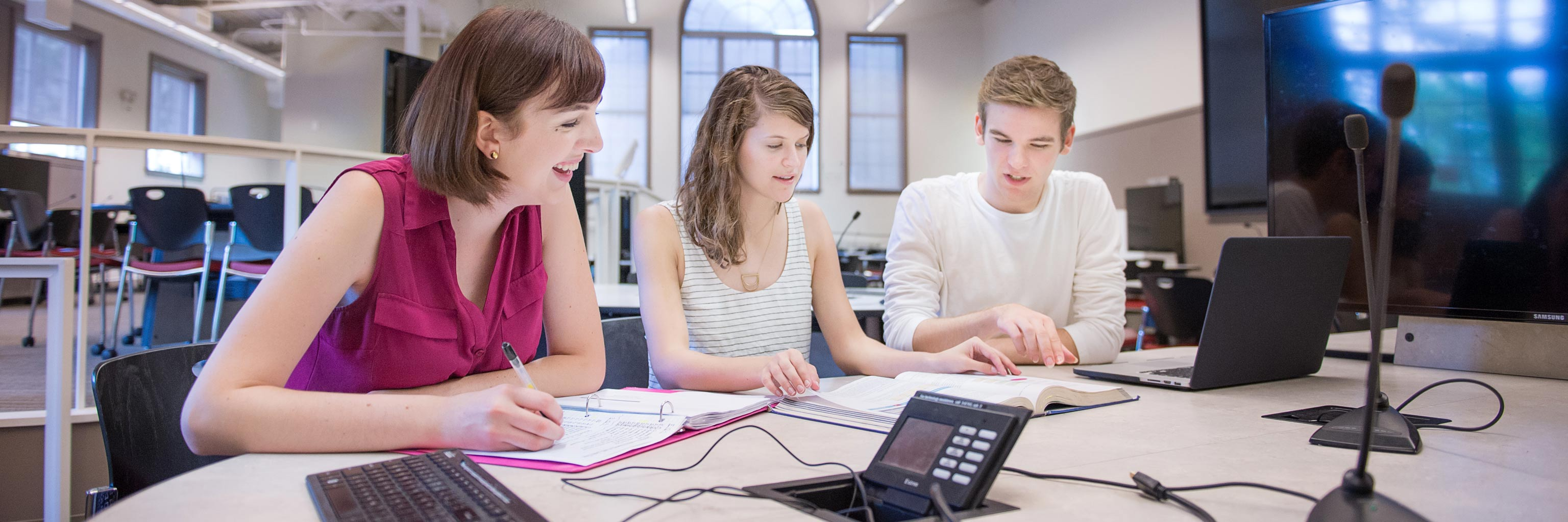 Three students working together around a table