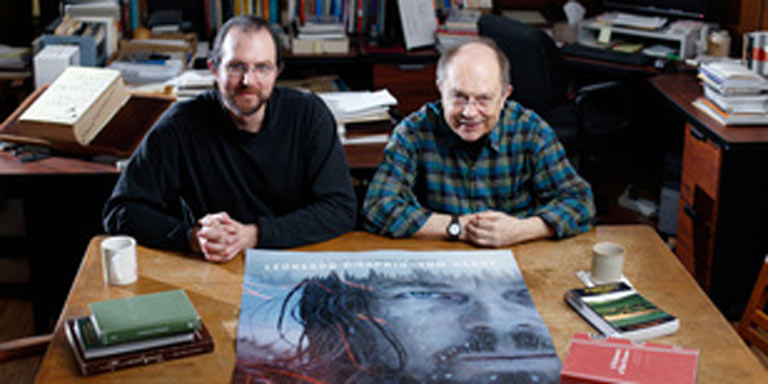 Two men sitting with a Revenant poster