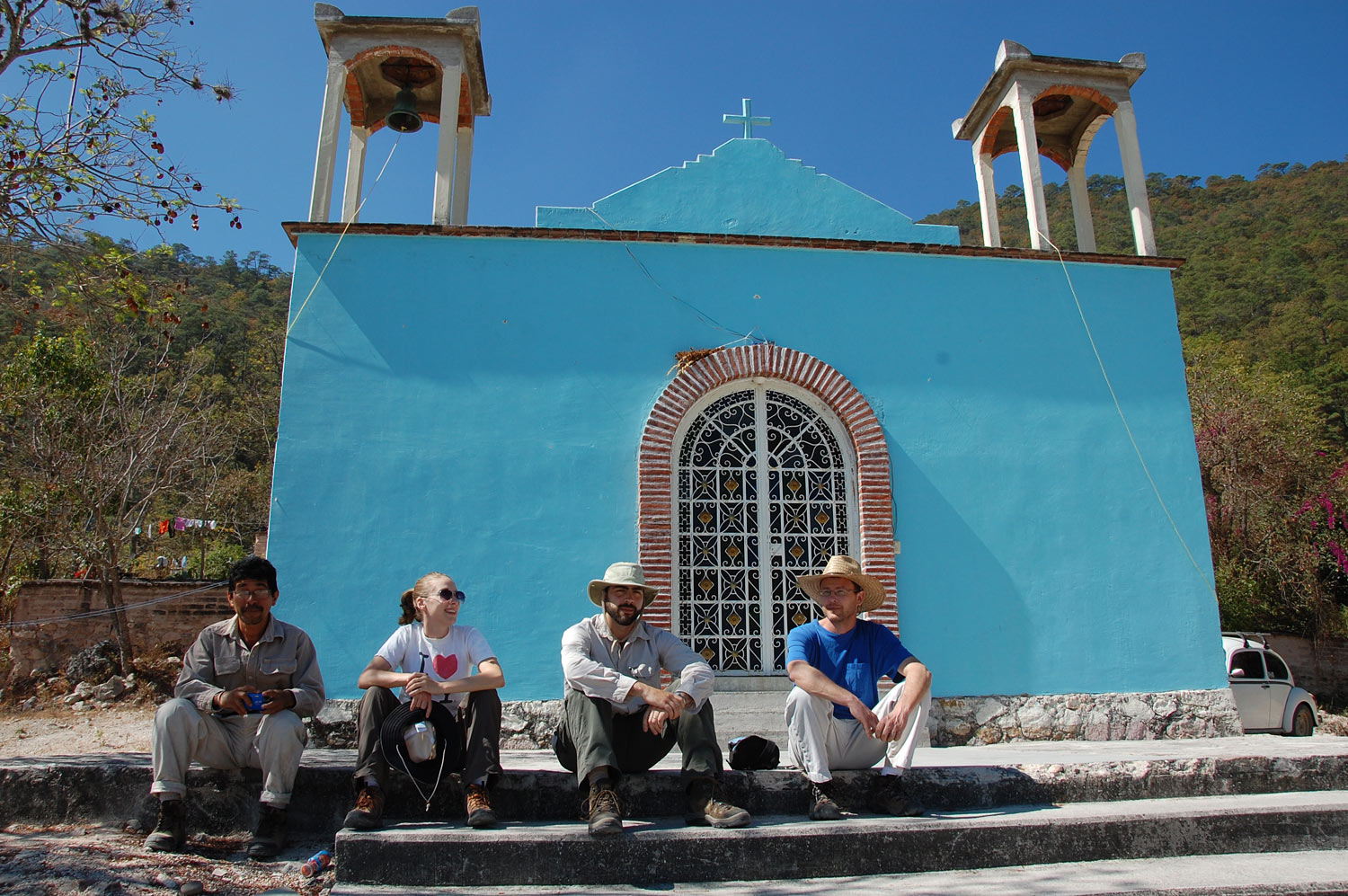 Four people sitting in front of a church
