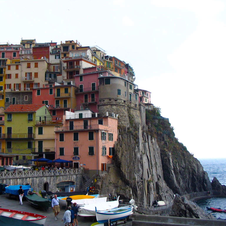 Boats and houses built into the side of a cliff