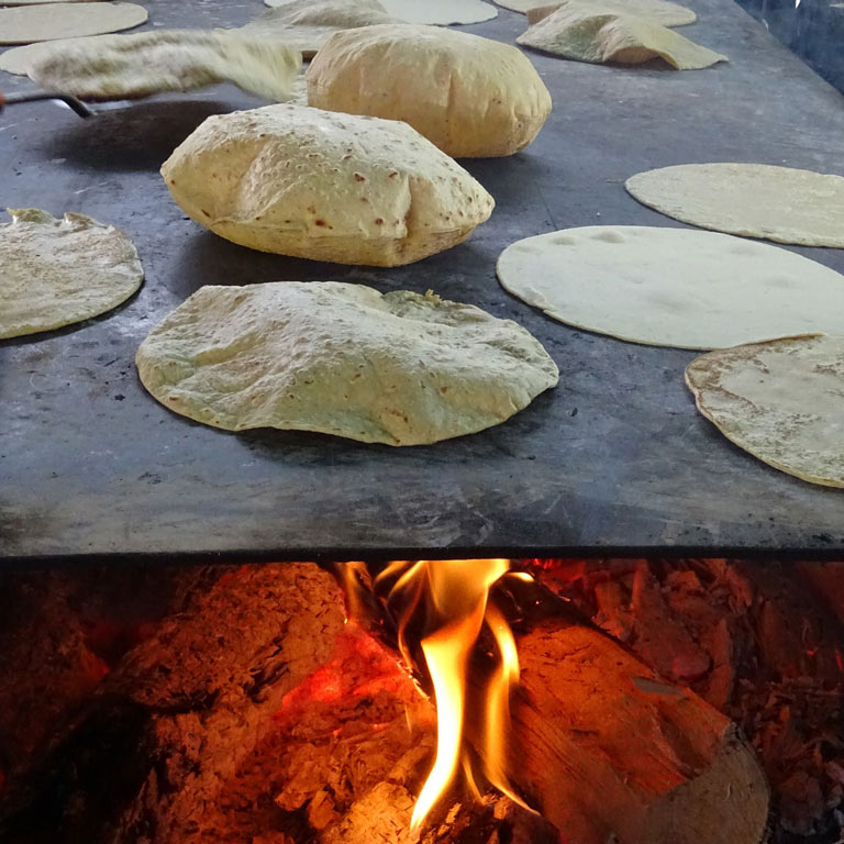 Tortillas cooking over a fire