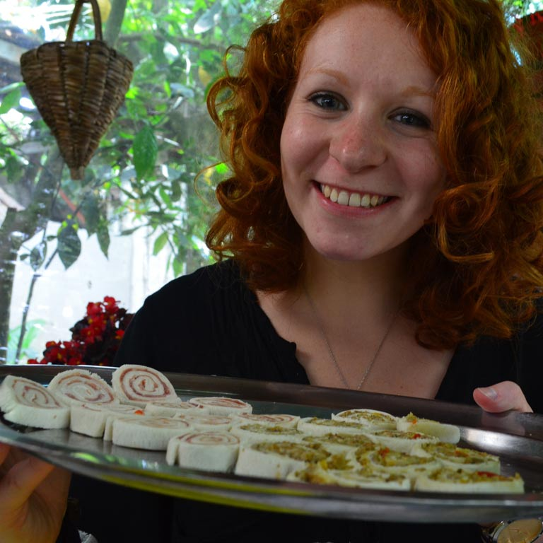 A woman smiling and carrying a tray of food samples